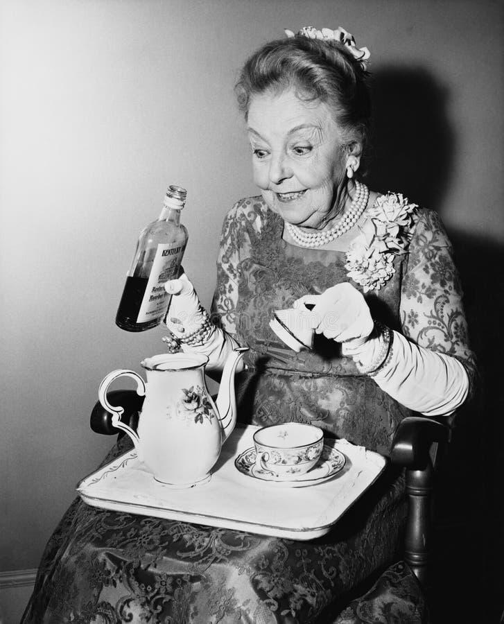 Femme agée clouant son thé (toutes les personnes représentées ne sont pas plus long vivantes et aucun domaine n'existe Garanties  images libres de droits