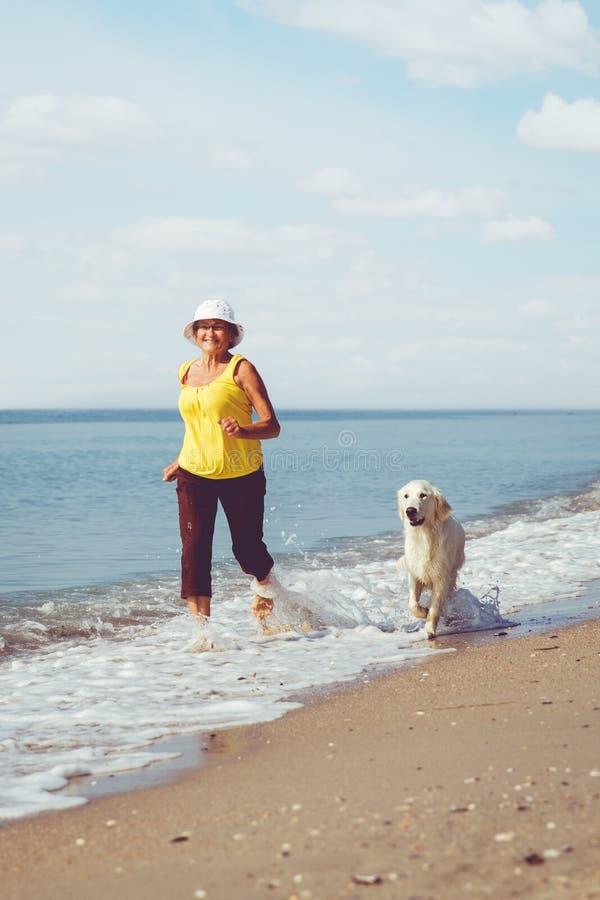 Femme agée courant avec son chien d'arrêt de golder image libre de droits