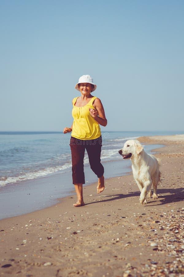 Femme agée courant avec son chien d'arrêt de golder photographie stock libre de droits