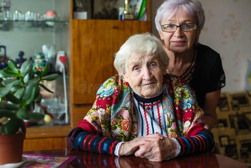 Femme agée dans des vêtements lumineux avec sa fille adulte s'asseyant à la table photos libres de droits