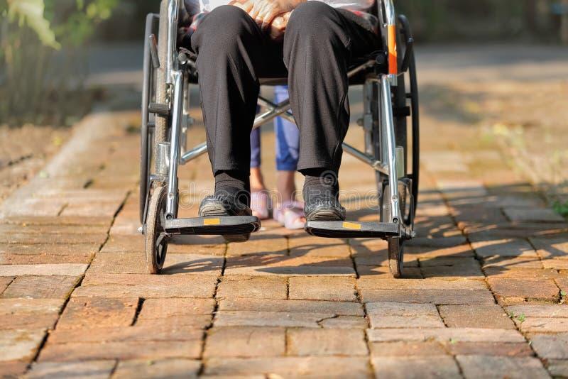 Femme agée dans le fauteuil roulant avec le travailleur social photos libres de droits