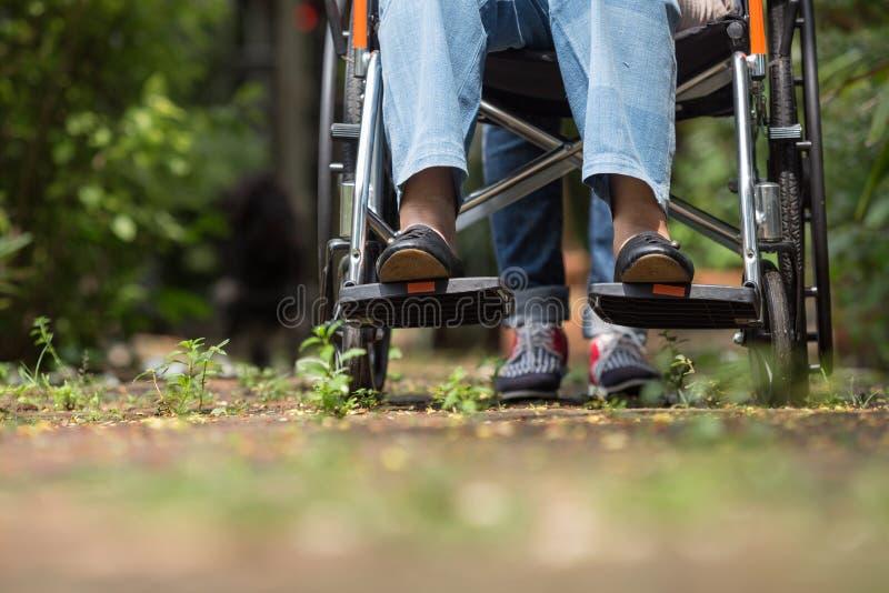 Femme agée dans le fauteuil roulant marchant avec la voiture photo libre de droits
