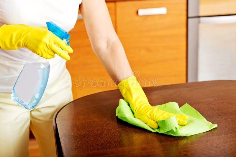 Femme agée dans les gants jaunes nettoyant la table photo stock