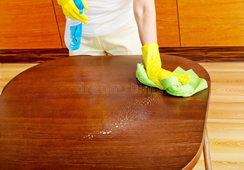 Femme agée dans les gants jaunes nettoyant la table image stock