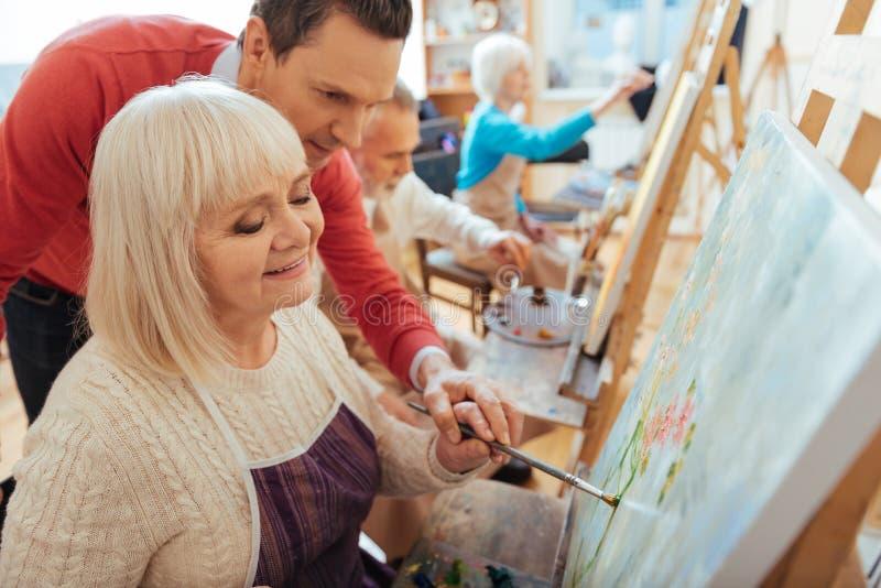 Femme agée de aide d'heureux homme dans le studio de peinture image libre de droits