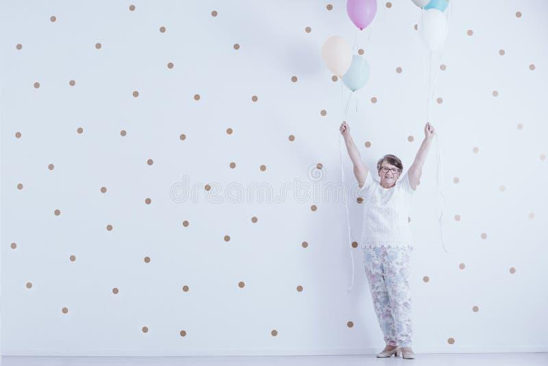 Femme agée de sourire positive avec les ballons colorés contre le wh images stock