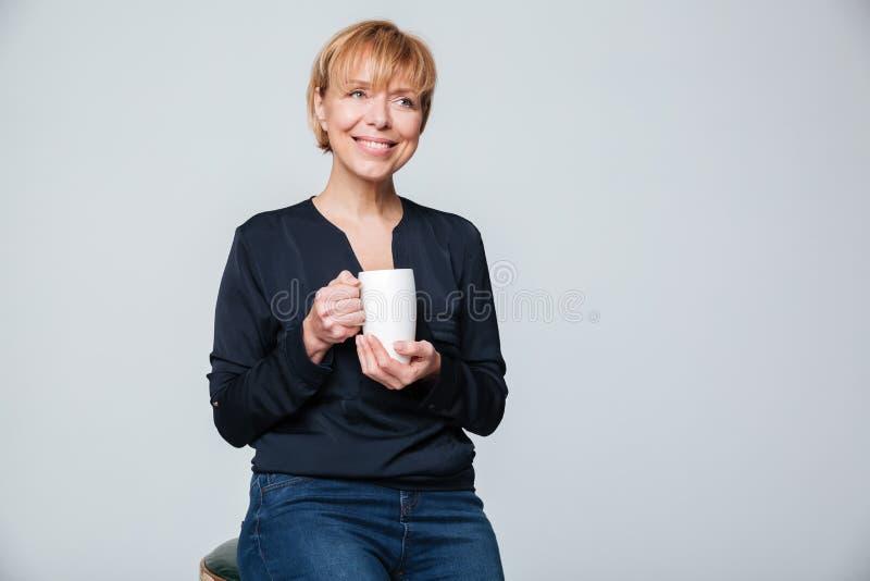 Femme agée de sourire tenant la tasse de thé image stock