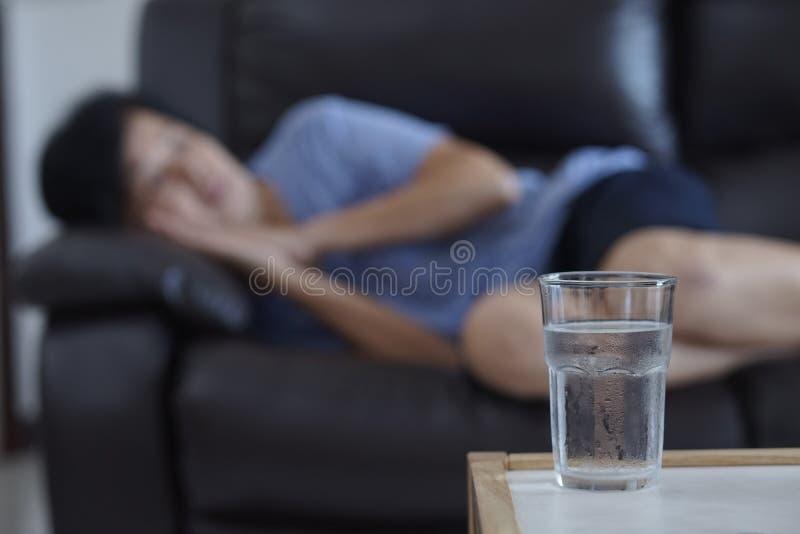 Femme agée dormant à la maison l'eau en verre sur le retir de sommeil de table photographie stock libre de droits