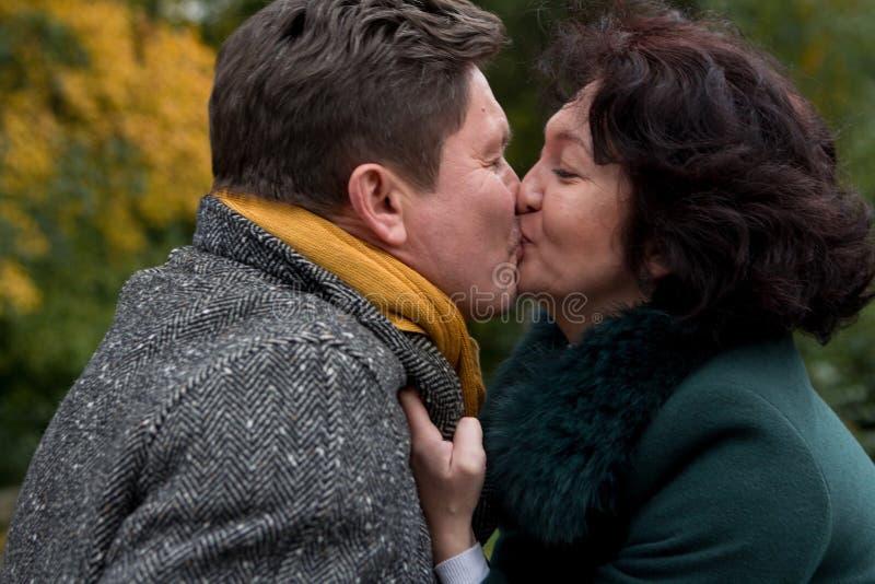 Femme agée embrassant un homme plus âgé tenue de détente Amour vrai photos stock