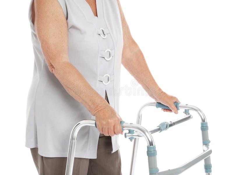 Femme agée employant le cadre de marche d'isolement sur le blanc images stock