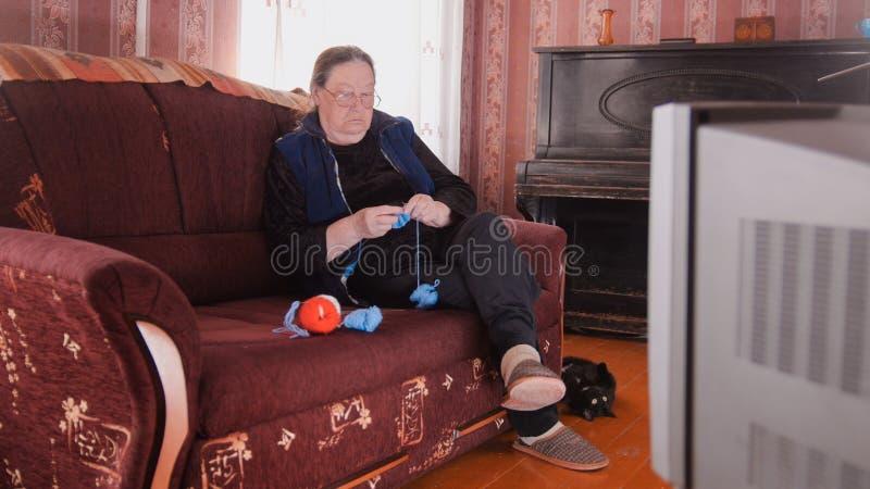 Femme agée en verres tricotant devant la TV image stock