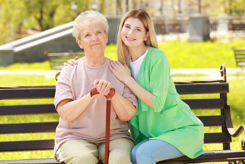 Femme agée et jeune travailleur social en parc images stock