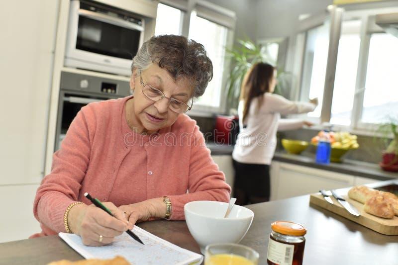 Femme agée faisant des mots croisé dans la cuisine photos libres de droits
