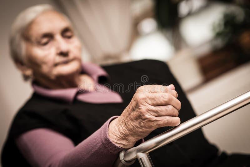 Femme agée fatiguée - foyer en main image libre de droits