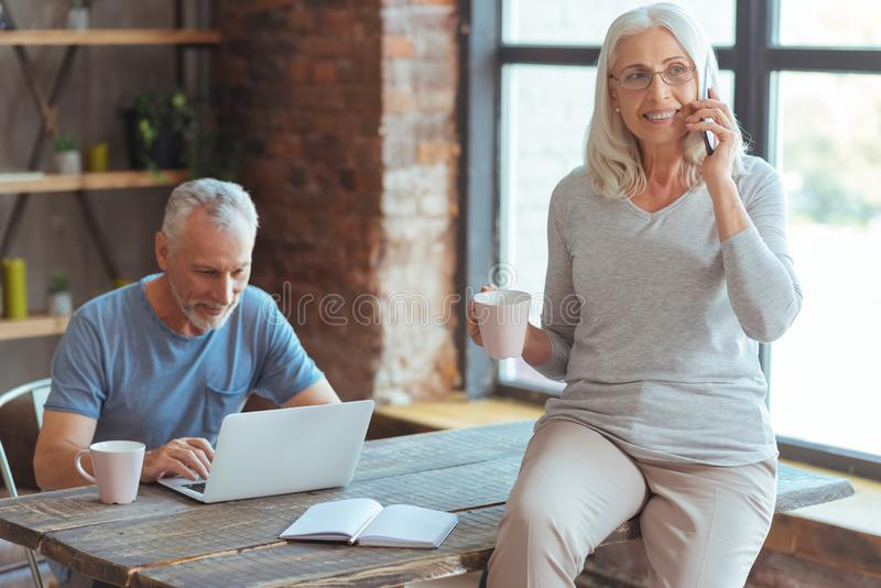 Femme agée gaie parlant au téléphone intelligent à la maison photo stock