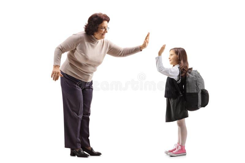 Femme agée haute-fiving une écolière photo libre de droits