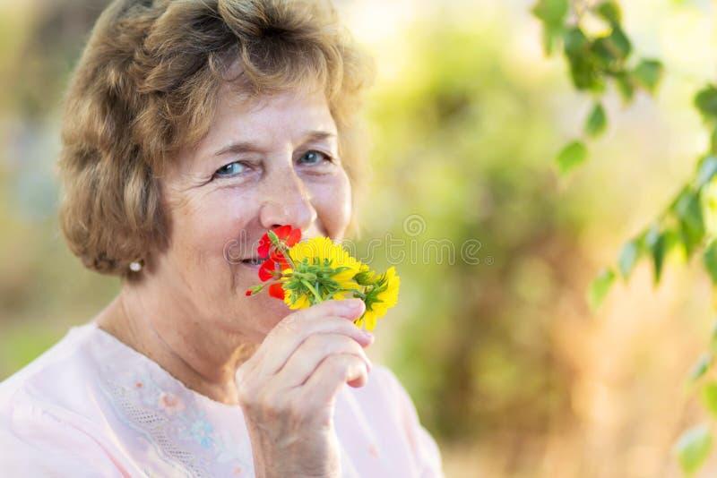 Femme agée heureuse avec des fleurs images stock