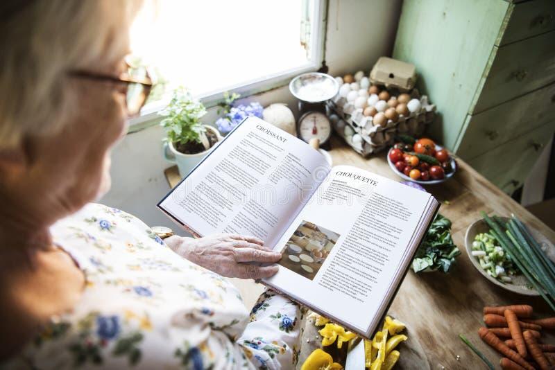Femme agée heureuse lisant un livre de cuisine images stock