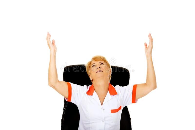 Femme agée heureuse s'asseyant derrière le bureau avec des mains  photo stock