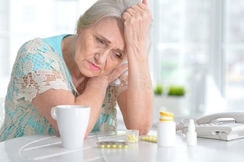 Femme agée malade avec le médicament images stock