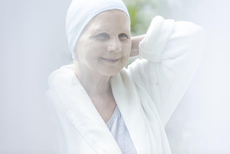 Femme agée malade heureuse et souriante avec le cancer photographie stock