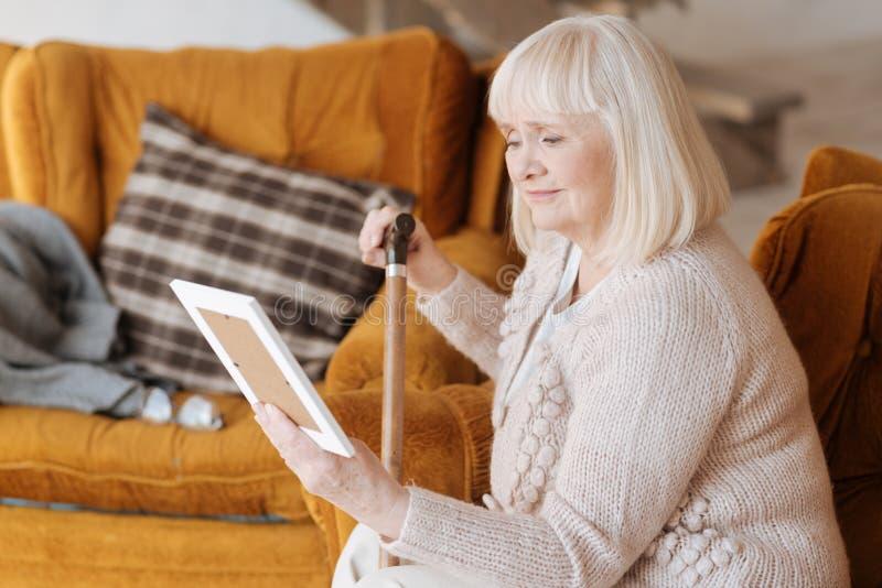 Femme agée malheureuse tenant une photographie photographie stock