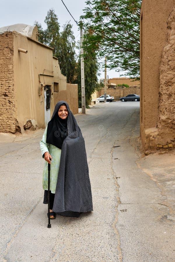 Femme agée musulmane, habillée dans le tchador noir sur la rue de la vieille ville dans Yazd l'iran photographie stock