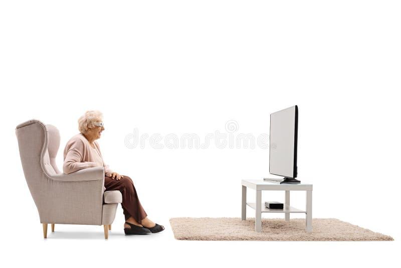 Femme agée portant une paire de lunettes 3D et observant le televisi photo stock