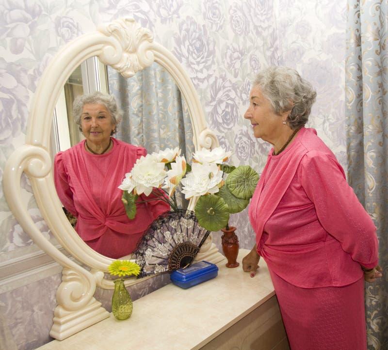 Femme agée près de miroir photo libre de droits