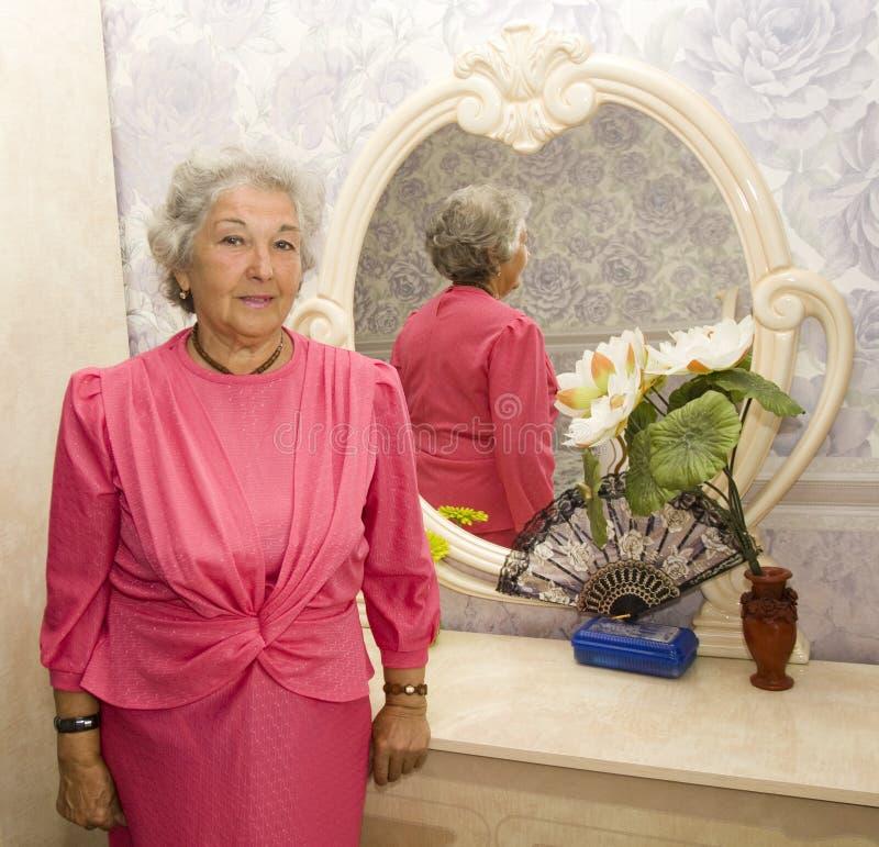 Femme agée près de miroir images stock