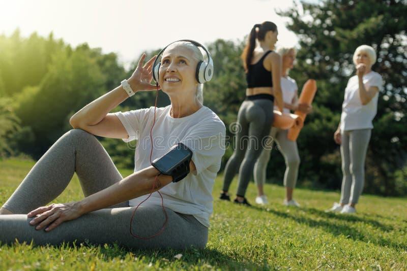 Femme agée rêveuse écoutant la musique avant la formation image stock