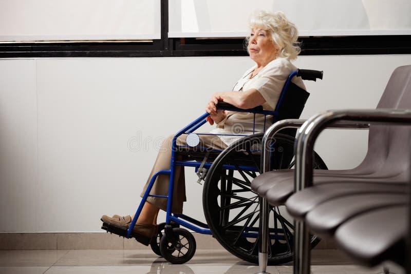 Femme agée songeuse sur le fauteuil roulant image libre de droits