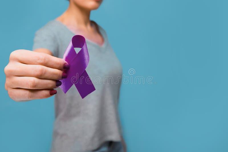 Femme agée tenant l'espace pourpre de copie de la conscience W de ruban Le symbole est employé pour soulever la conscience pour l image libre de droits