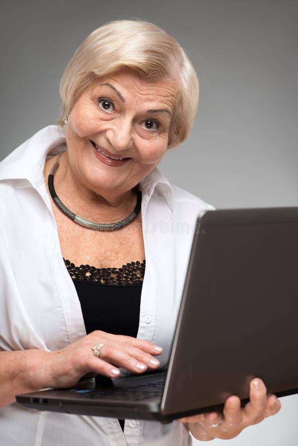Femme agée tenant l'ordinateur portable photo libre de droits