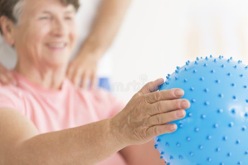 Femme agée tenant la boule bleue photographie stock libre de droits