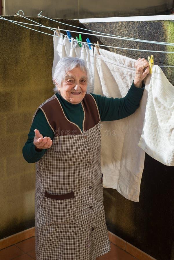 Femme agée traînant le lavage sur la terrasse photographie stock libre de droits