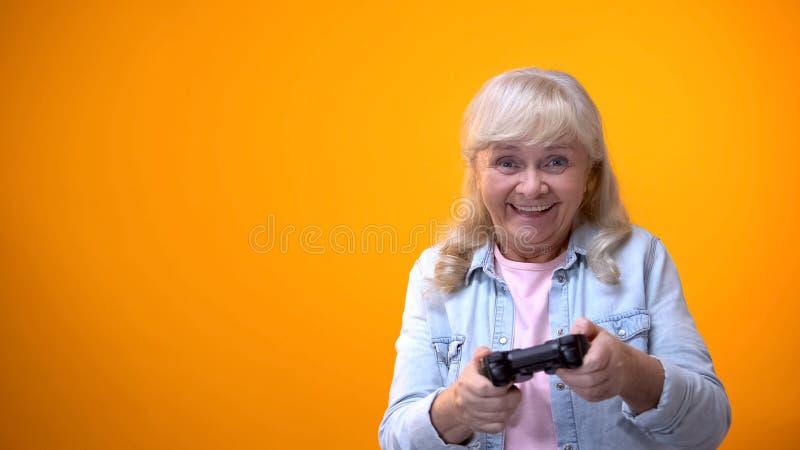 Femme ag?e optimiste active jouant le jeu d'ordinateur, manette de participation, instrument photos stock