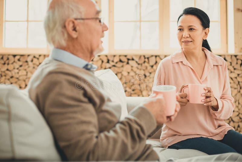 Femme agréable et sa vieille salle buvant du thé chaud des tasses roses photos stock