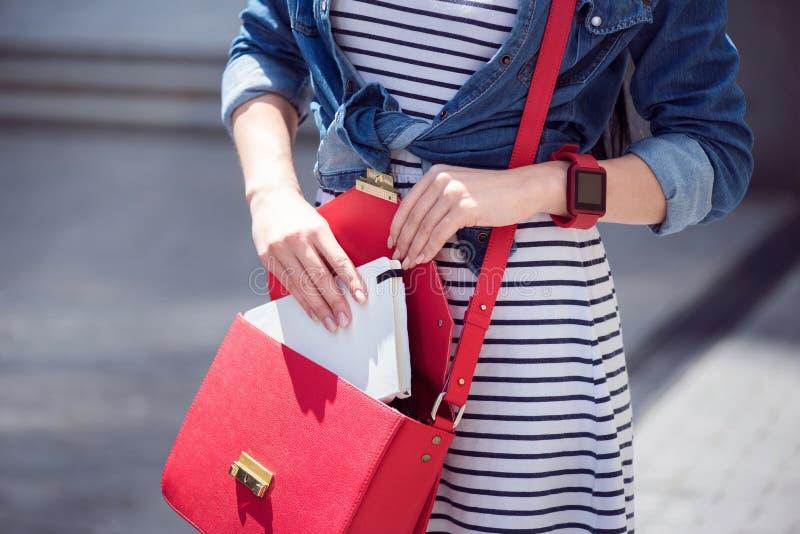 Femme agréable mettant le livre dans son sac photo stock