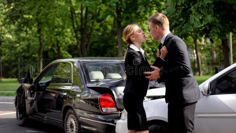 Femme agressive pressant un conducteur masculin coupable, collision de véhicules, conflit routier photos stock