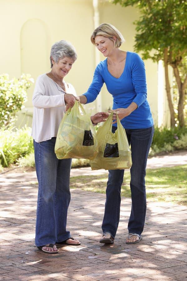 Femme aidant la femelle supérieure avec des achats photo libre de droits