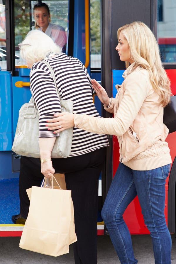 Femme aidant la femme supérieure à monter à bord de l'autobus photographie stock