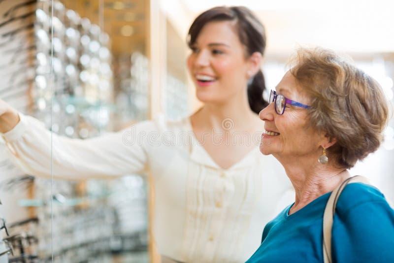 Femme aidant le client supérieur en sélectionnant photos stock
