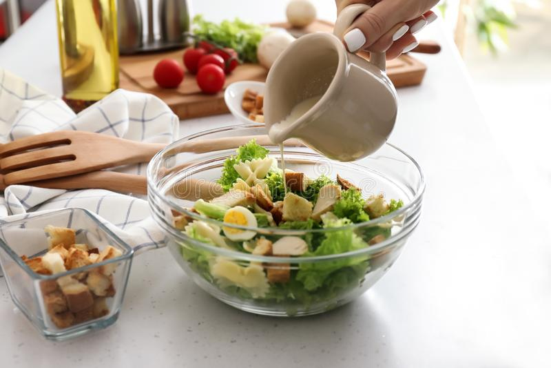 Femme ajoutant la sauce à la salade de César délicieuse avec des pâtes sur la table images stock