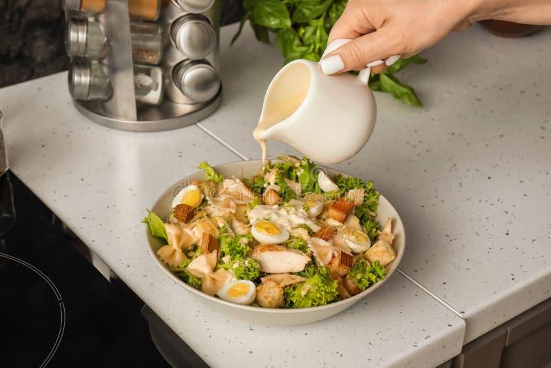 Femme ajoutant la sauce à la salade de César délicieuse avec des pâtes sur la table image libre de droits