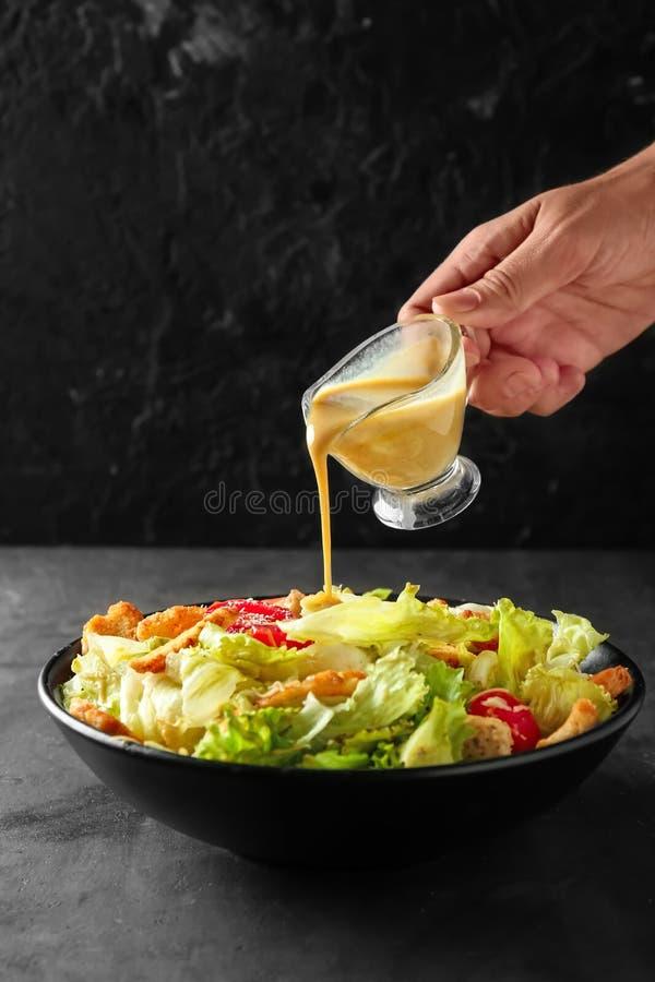 Femme ajoutant la sauce à la salade de César savoureuse dans la cuvette sur la table images libres de droits
