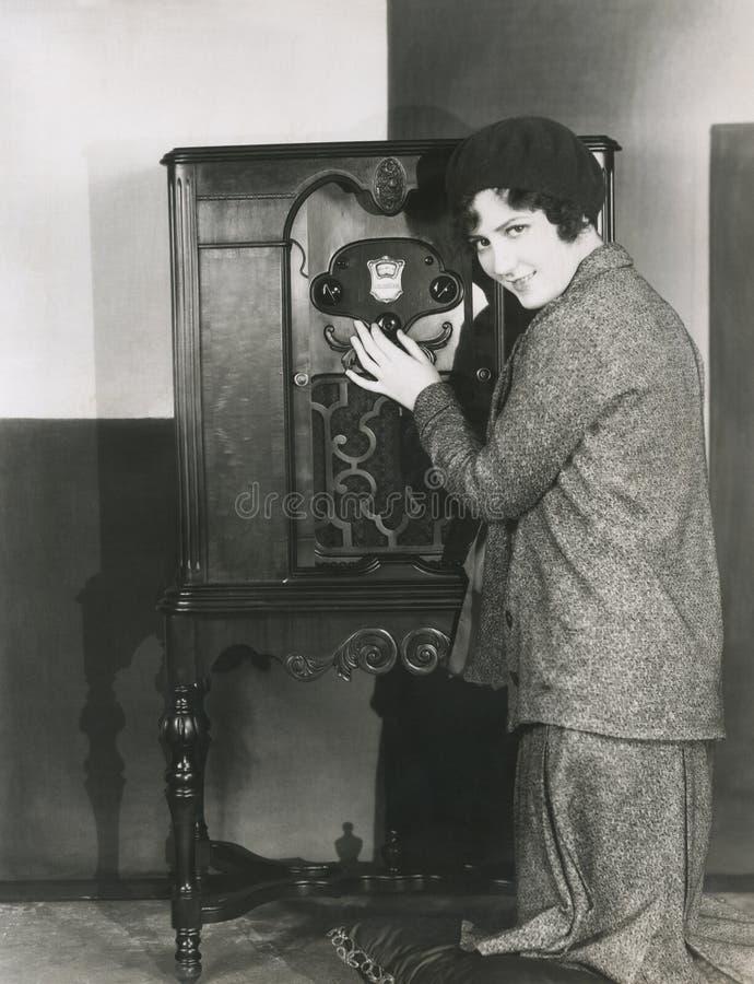 Femme ajustant la radio du volume le 1920 s image stock