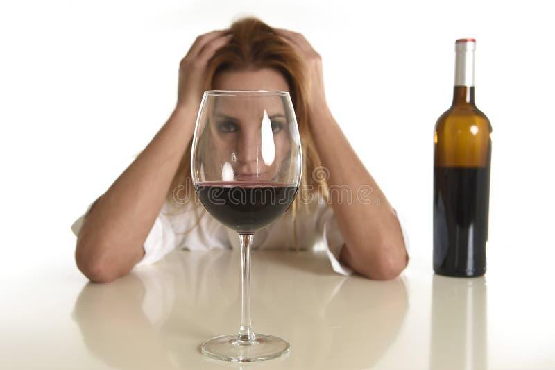 Femme alcoolique déprimée gaspillée blonde caucasienne buvant l'alcoolisme en verre de vin rouge photos stock