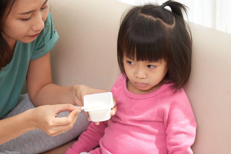 Femme alimentant la petite fille image libre de droits