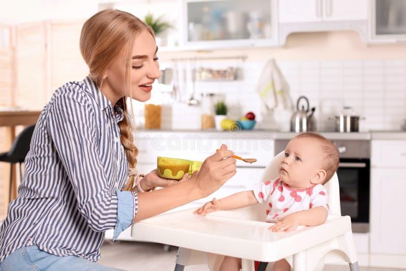 Femme alimentant son enfant dans le highchair à l'intérieur image libre de droits